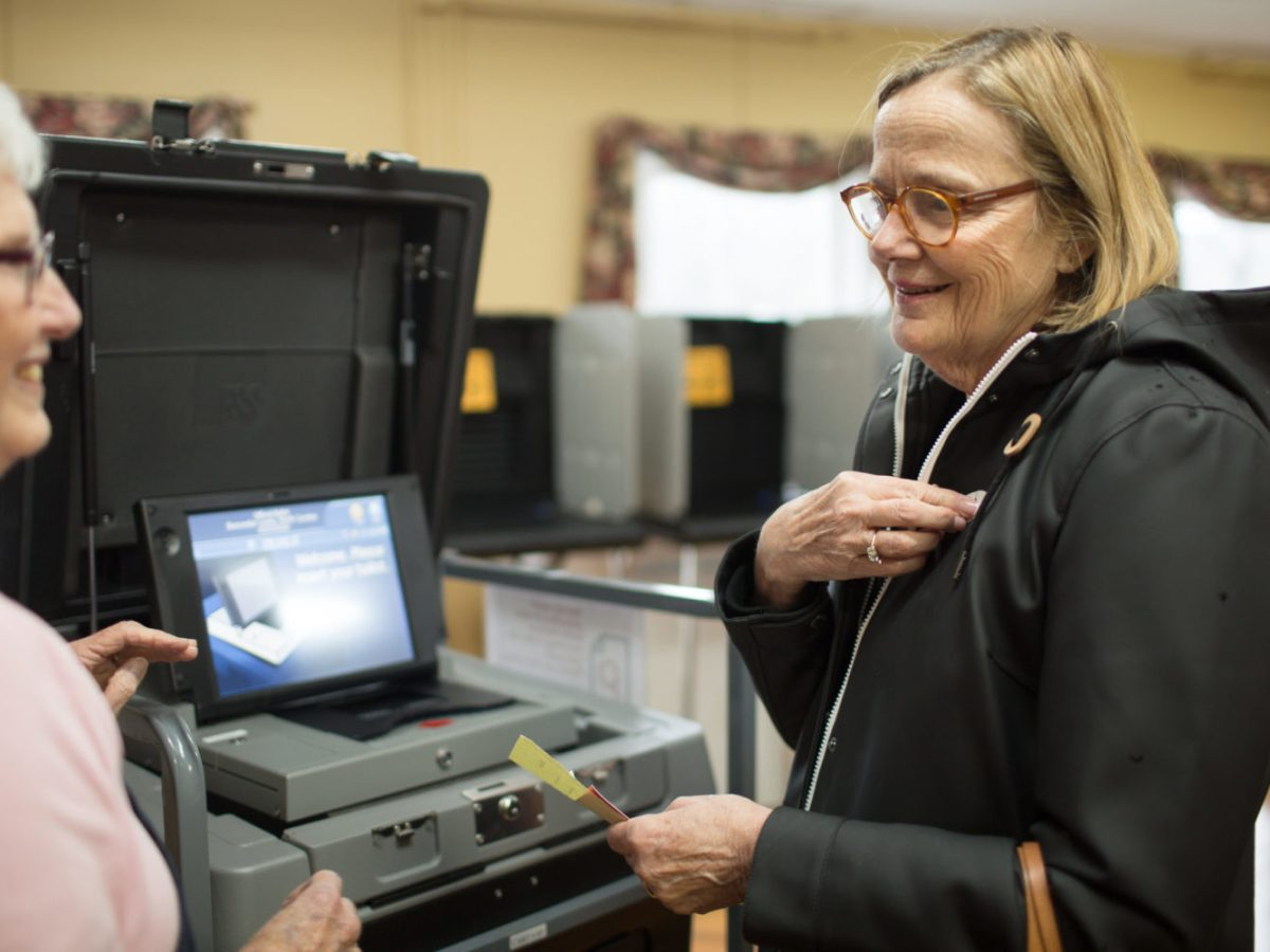 """Grace Nichols of Montreat puts on her """"I voted"""" sticker as she prepares to scan her 2020 primary election ballot at the First Baptist Church of Black Mountain polling place in Buncombe County on March 3, 2020. Colby Rabon / Carolina Public Press"""