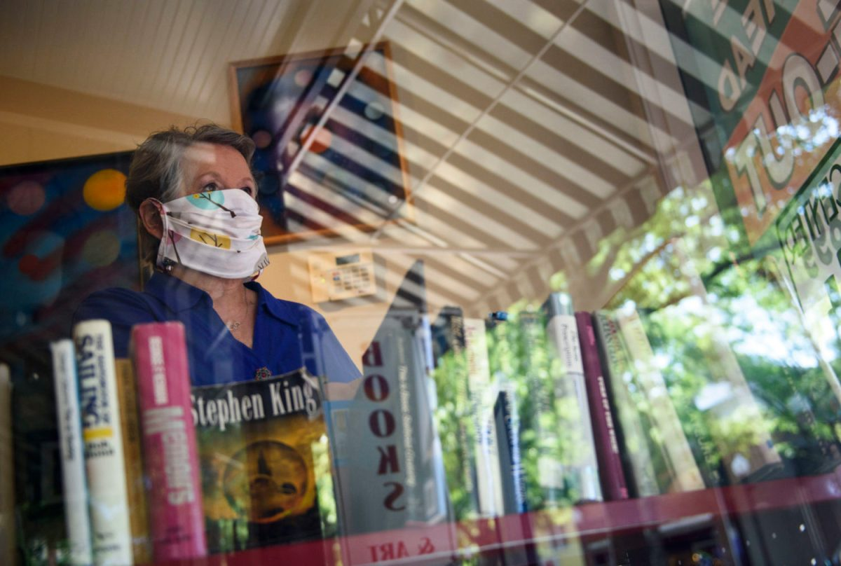 Diane Parfitt looks out the window of her store City Center Gallery & Books in Fayetteville on Monday. Parfitt's shop has gone through the process of reopening in recent days, returning to mostly regular hours with the requirement that customers wear masks while they shop. Melissa Sue Gerrits / The Carolina Public Press