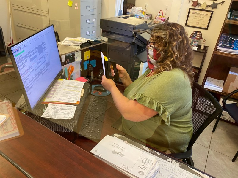 Lori Huskins, deputy director of Mitchell County's elections office, scans the bar code that identifies the voter who submitted a mail-in ballot. Victoria Loe Hicks / Carolina Public Press