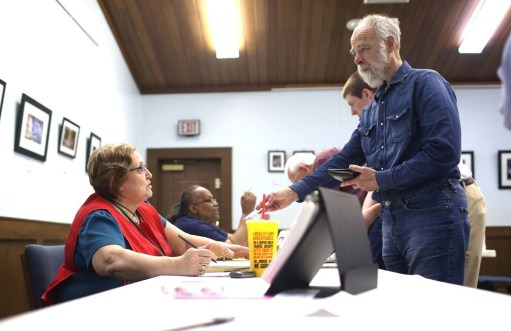 Haywood County precinct Chief Judge Debbie Stamey interacts with David Cairnes as he presents his photo ID at the Canton Public Library to vote in the March 15, 2016 primary election. (Colby Rabon / Carolina Public Press)
