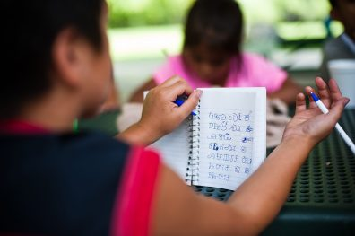 """A notebook with Cherokee Syllabary is seen during a lesson at Cherokee Language and Culture Camp held at Big Cove Recreation Center in Cherokee, NC on Monday, July 9. """"First and foremost is to save our language,"""" says Driver. Kids at the camp practice traditional arts as well as learning the Cherokee language and syllabary. (Mike Belleme for Carolina Public Press)"""