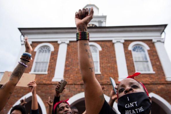 """A woman holds her fist up while shouting """"no justice, no peace"""" during demonstrations Saturday at the historic Market Square in downtown Fayetteville in reaction to the death of George Floyd. (Melissa Sue Gerrits / The Carolina Public Press)"""
