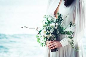 Gros plan sur le bouquet et la bague portés par la mariée