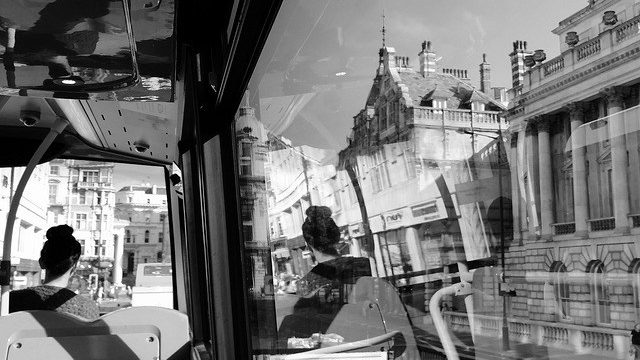woman alone on bus with distorted reflections in windows