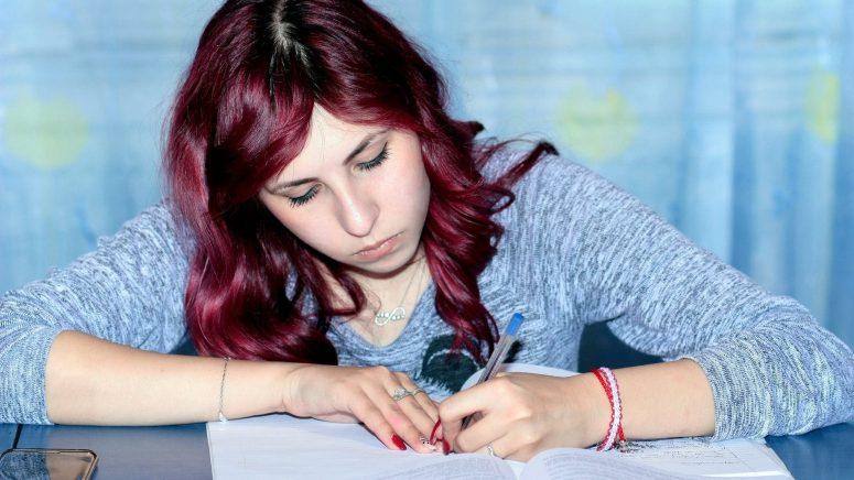 girl writing exam paper