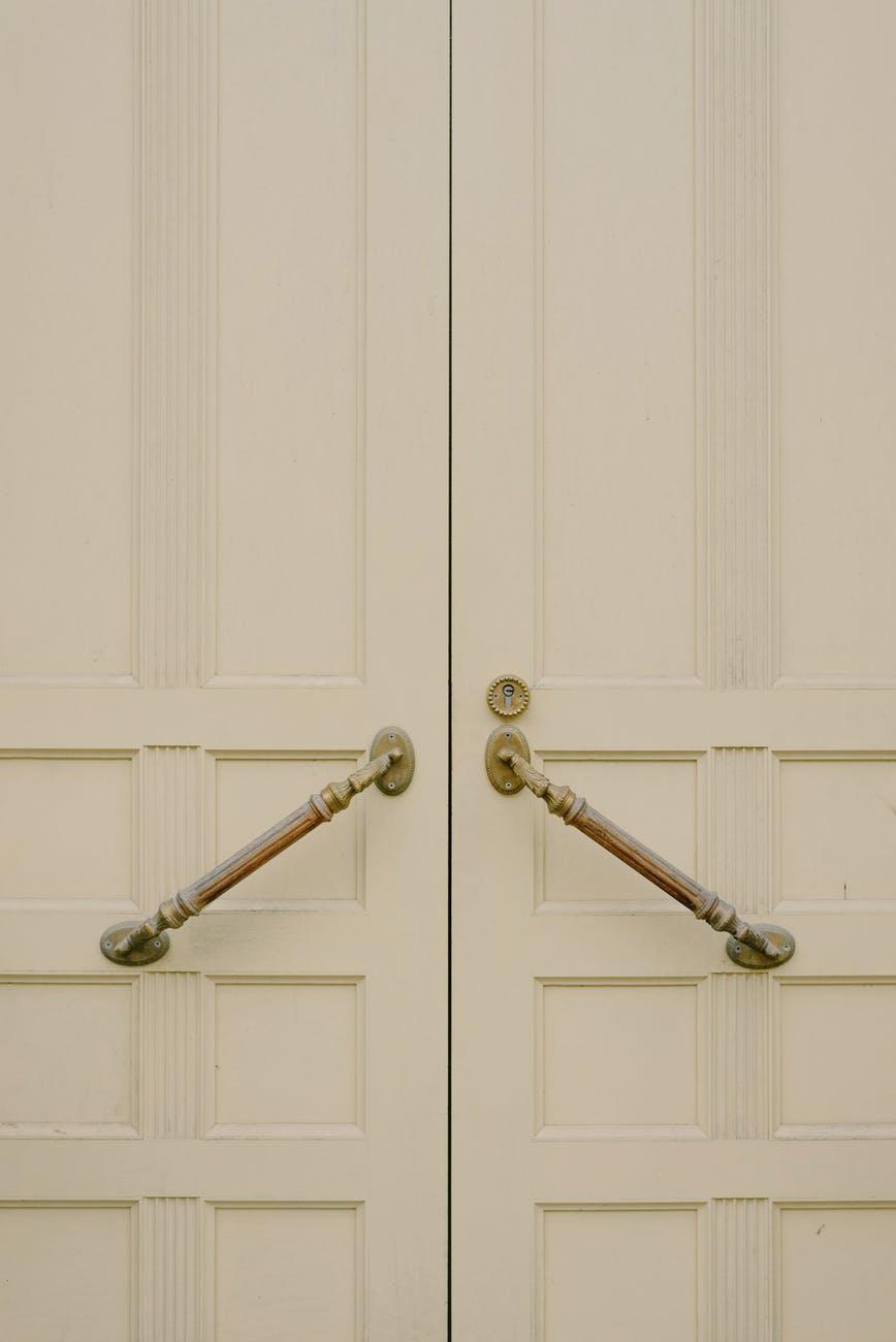 white wooden door with metal handles