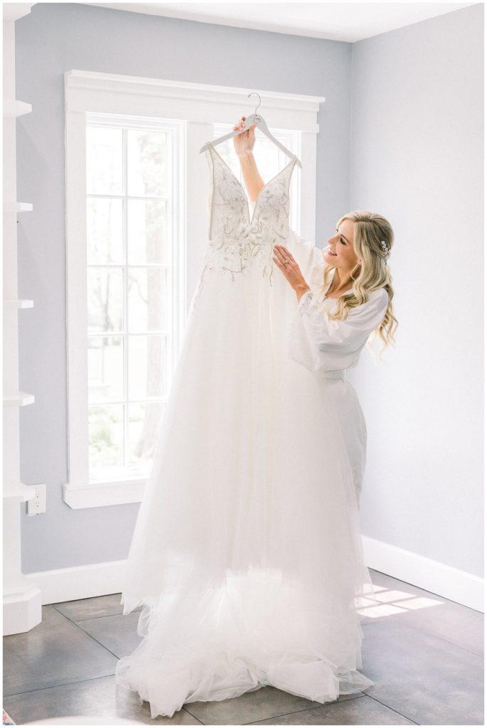 bride admiring Hayley Paige wedding dress at Ryland Inn wedding