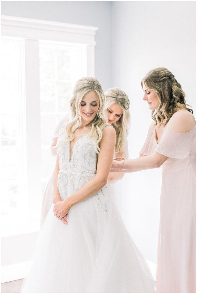 bride putting on Hayley Paige dress at Ryland Inn wedding