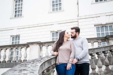 Couple leaning in for a kiss during engagement shoot on the steps of the Queen's House in Greenwich