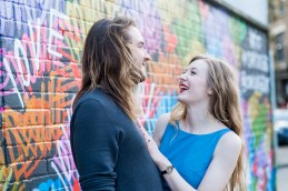 Couple laughing in front of colourful street art in Shoreditch