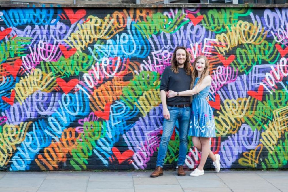 Couple stood in front of love street art
