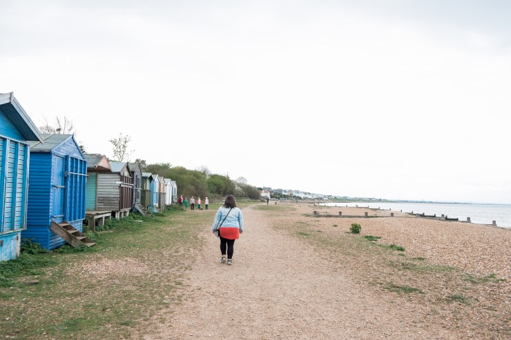 Young woman walking past colourful beach huts