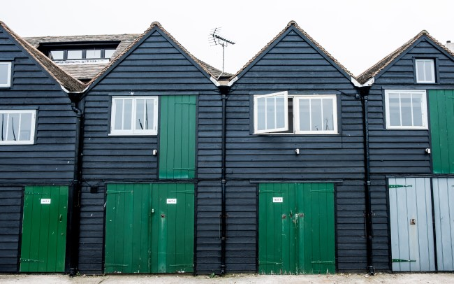 Black fish huts with green doors on Whitstable seafront