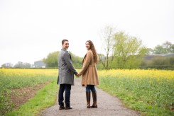Couple holding hands and walking through rapeseed field