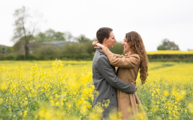 Couple laughing together in flowering field