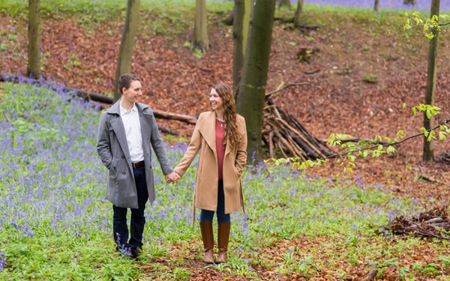 Couple holding hands in woods with bluebells