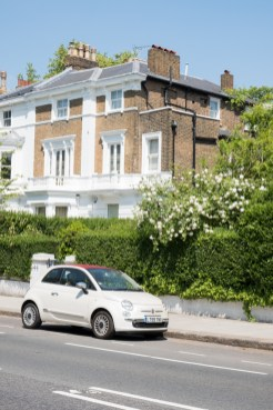 White Fiat in front of classic house in Kensington
