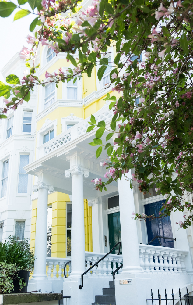 Bright yellow Victorian home with pink blossom