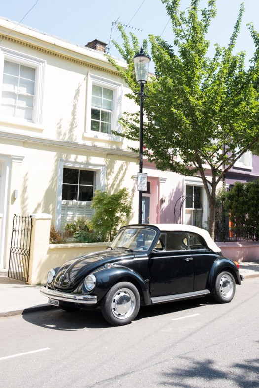 A classic car parked in front of a pastel house in Notting Hill