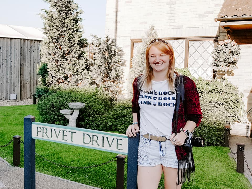 Bohemian girl posing next to the Privet Drive sign at