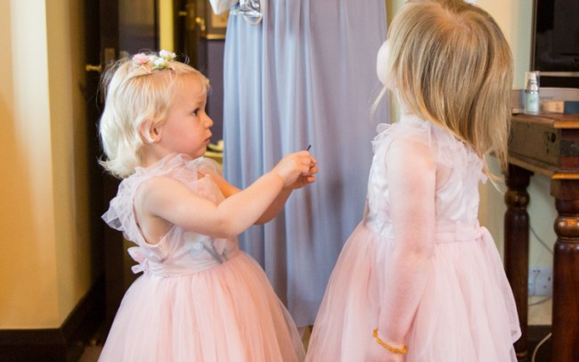 Two cute flower girls in pink dresses looking up at mum
