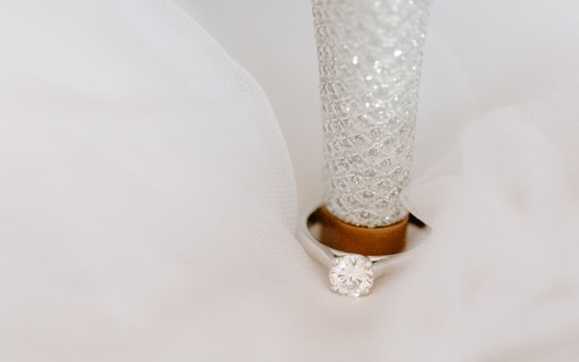 Macro image of engagement ring around the heel of wedding shoe