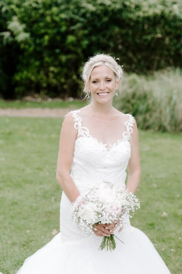Bride smiling at camera and holding bouquet