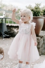 Cute flower girl in pink throwing confetti on herself