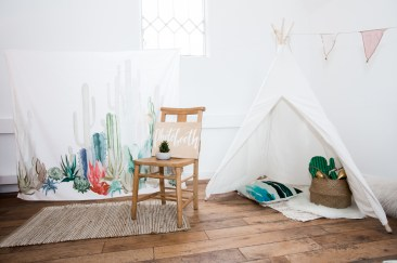A children's tepee with cacti toys in front of it