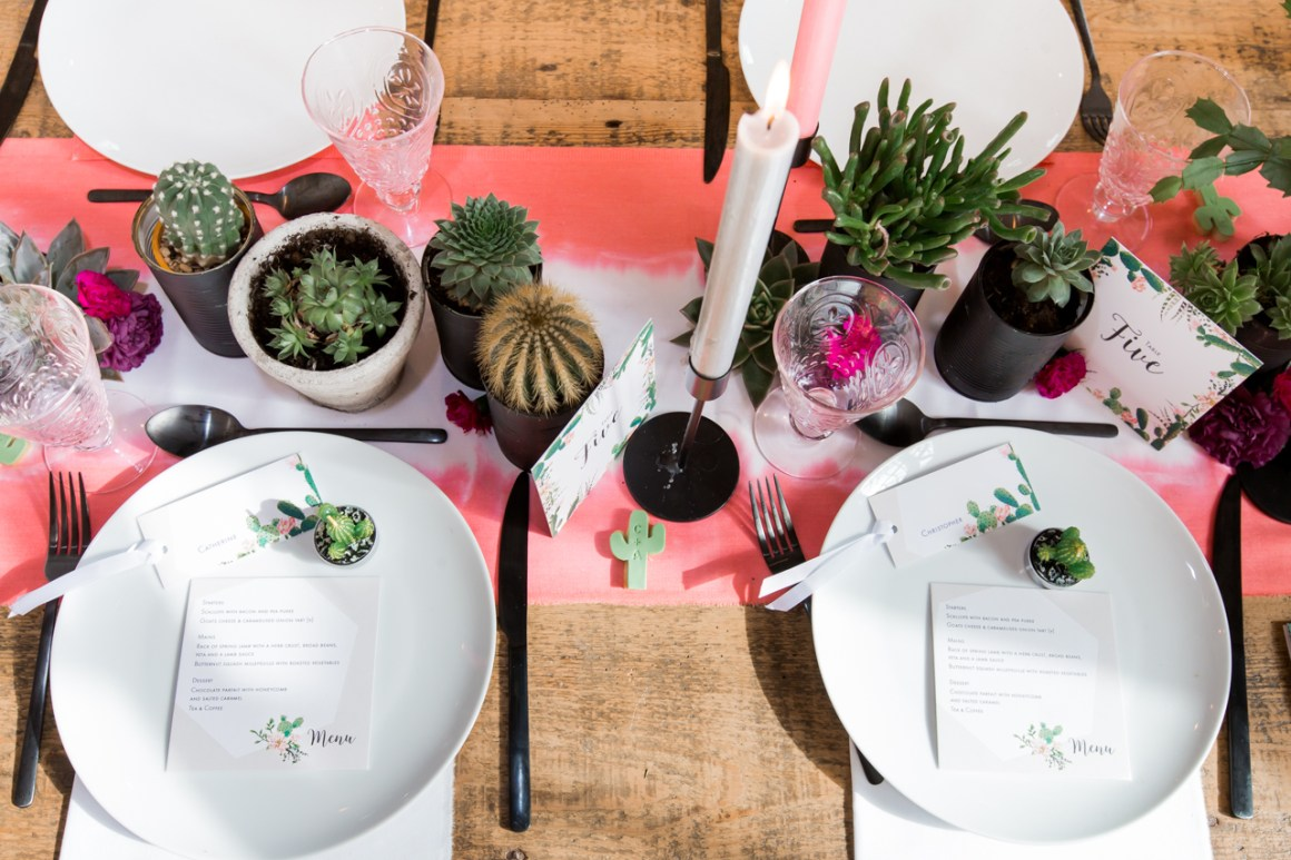 Wide shot of a wedding top table with a coral table runner and cacti decor