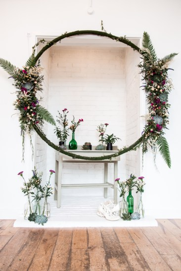 A beautiful hanging floral loop with green vases and purple flowers below