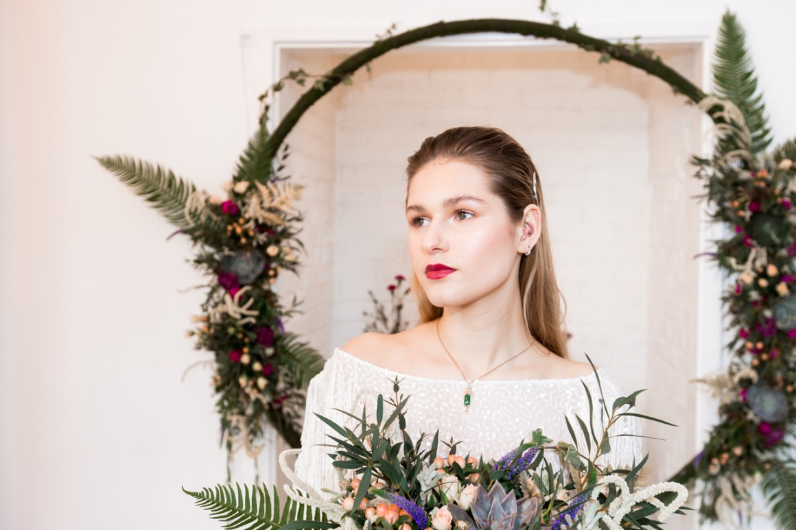 Beautiful bride stood in front of floral hoop and holding wild large bouquet