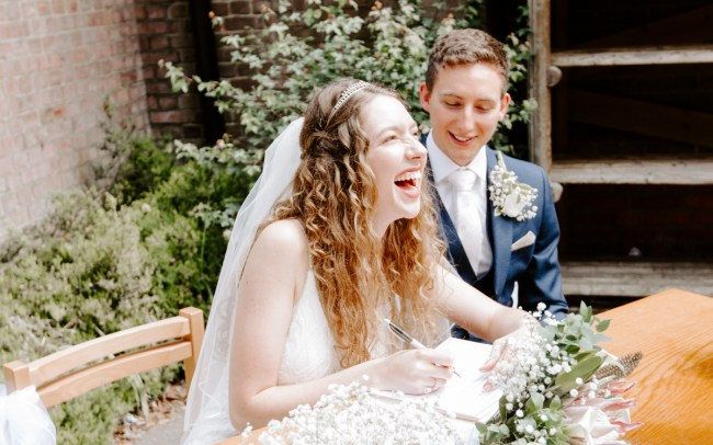 Laughing bride signing the register at wedding