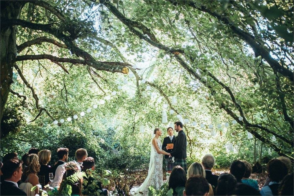 Bride and groom getting married under sunlit trees in England