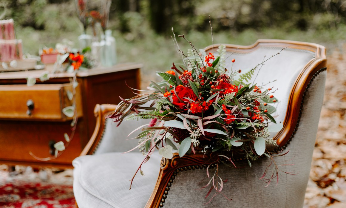 Large red wedding bouquet on an armchair in the woods