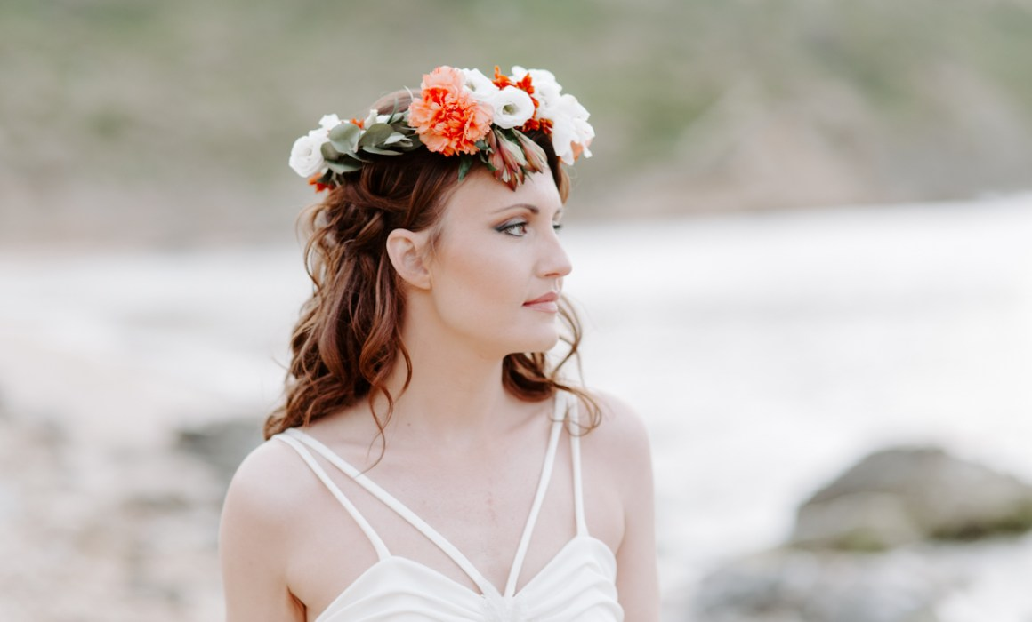 Bohemian bride wearing a floral crown and looking out to sea