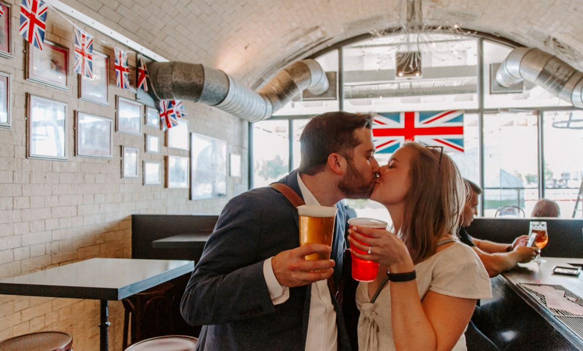 A newly engaged American couple kissing in British pub