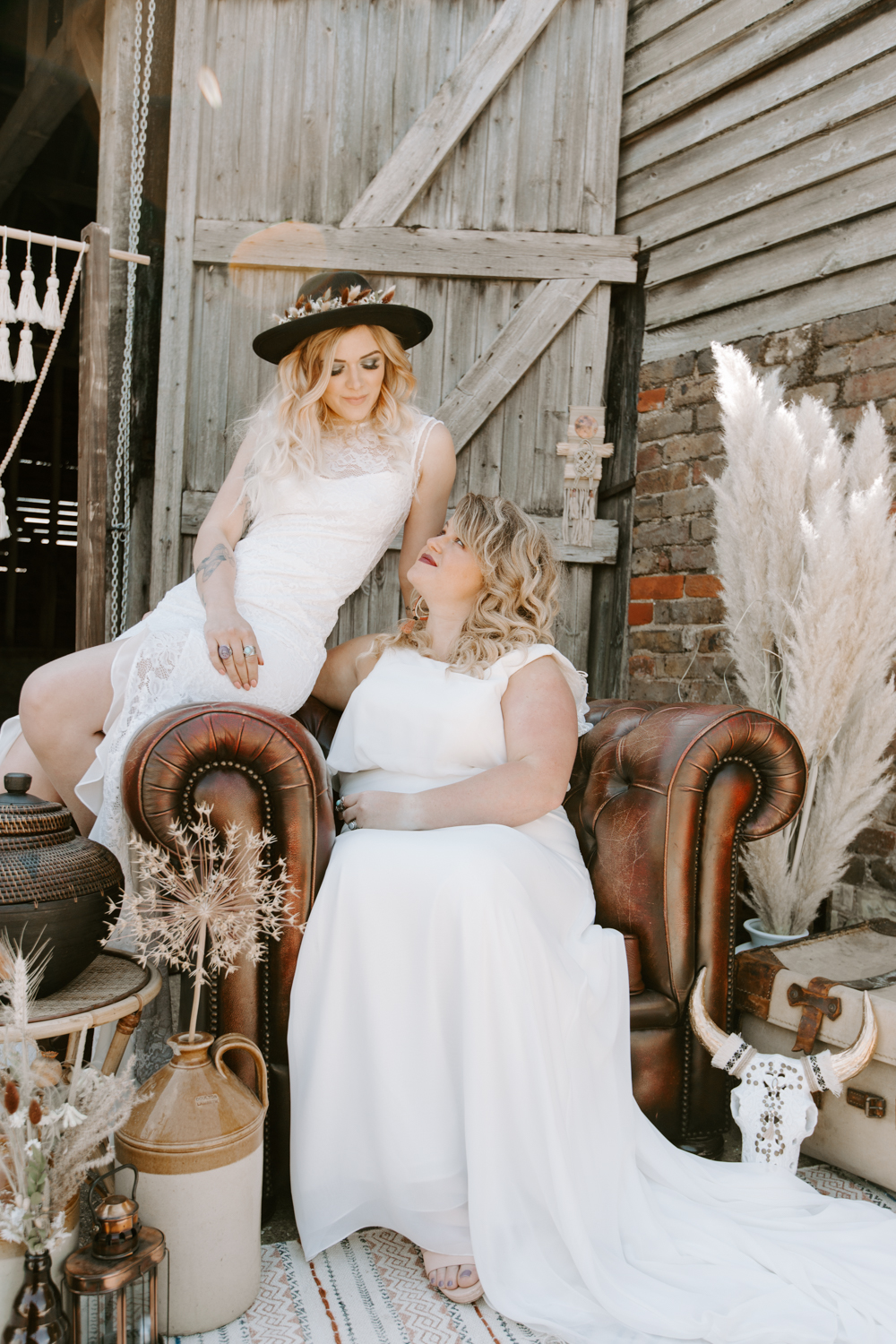 Two brides sat on a leather armchair and surrounded by florals