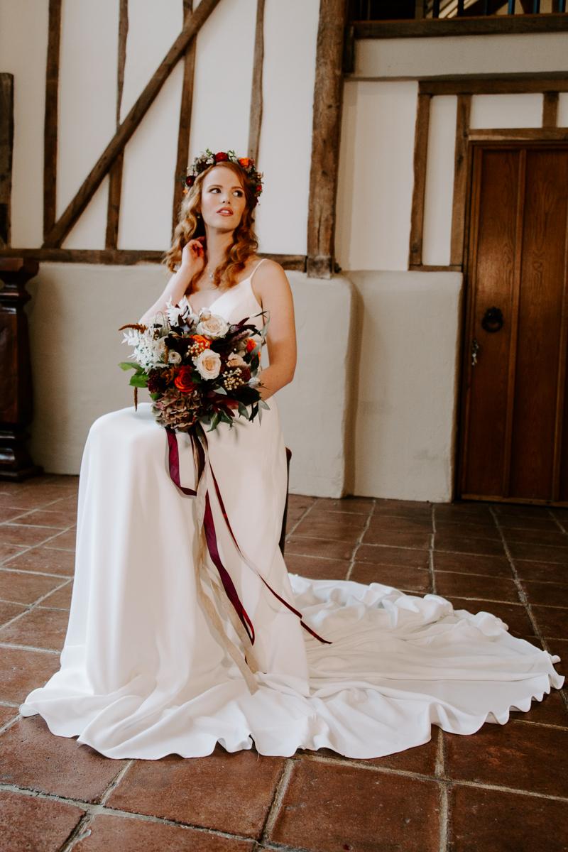Bride sat in barn wedding venue near London