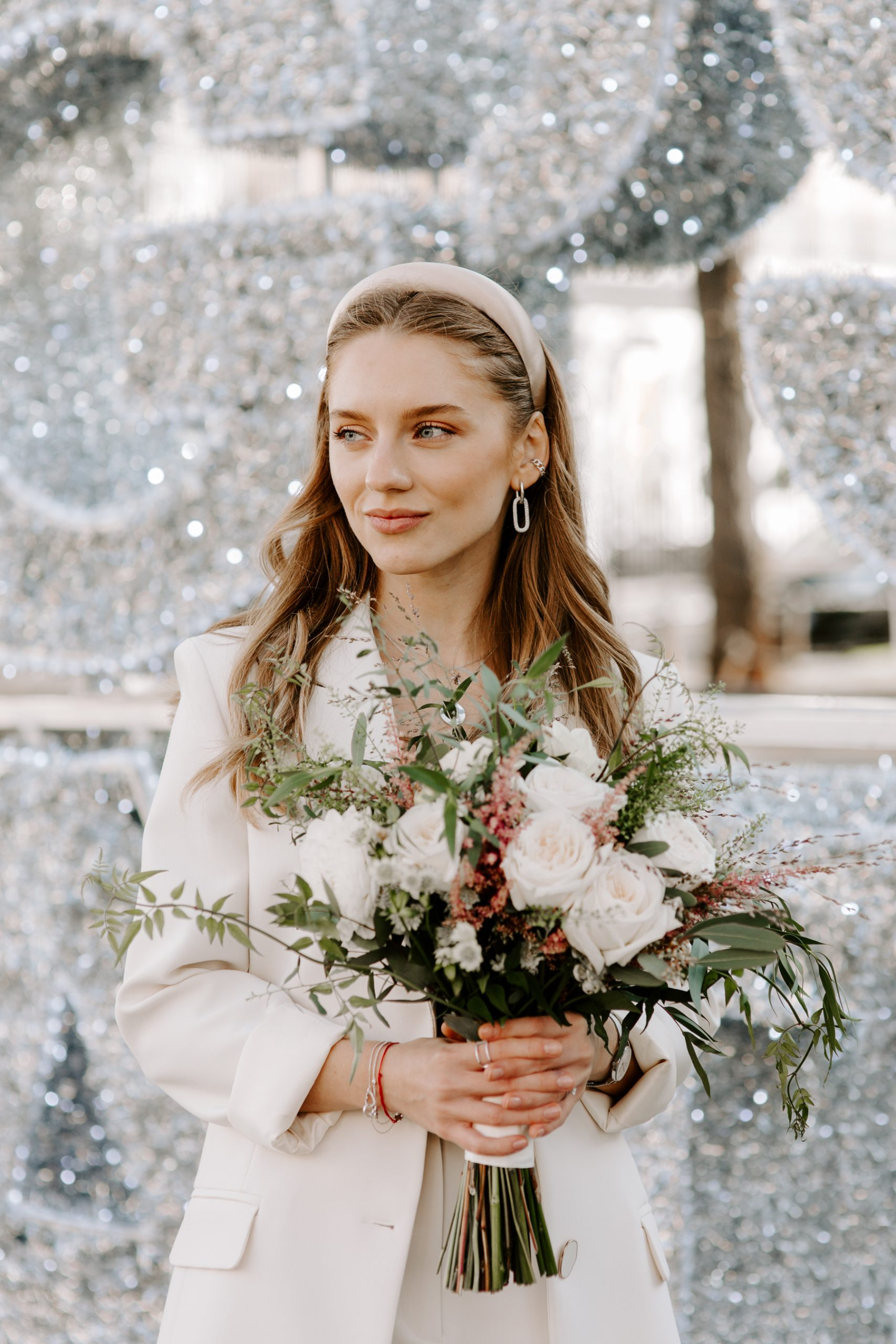 Bride holding a bouquet in front of London Christmas lights