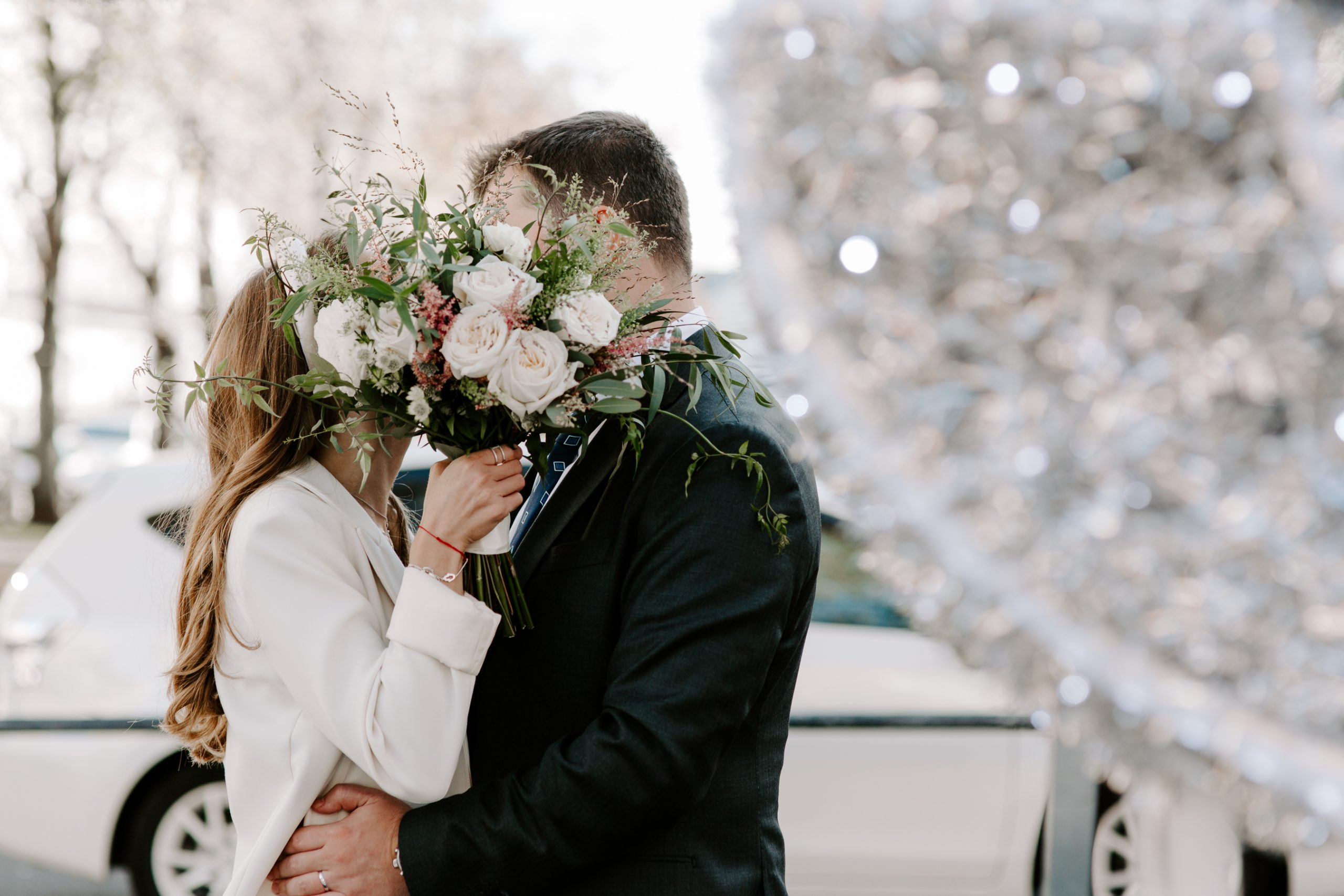 Bride and groom kissing behind wedding bouquet