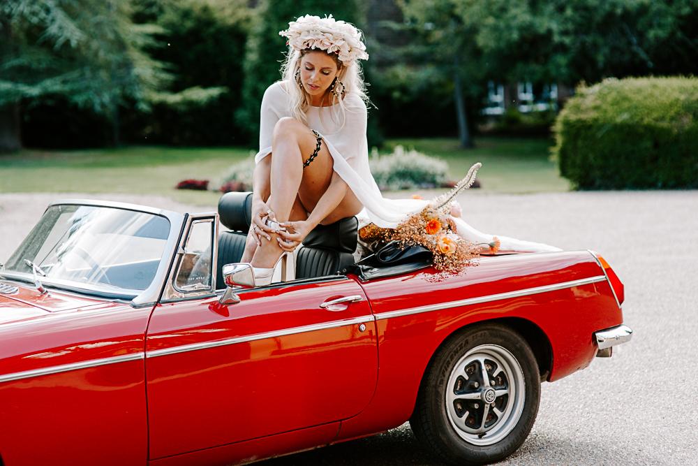 Bride sat on vintage car at Woldingham School