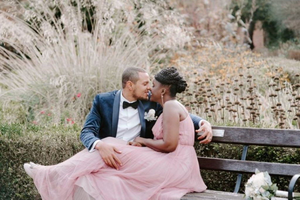 Bride in pink dress kissing groom at Valentines Mansion Redbridge
