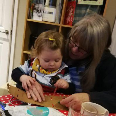 Caroline Skinner teaching young grandson