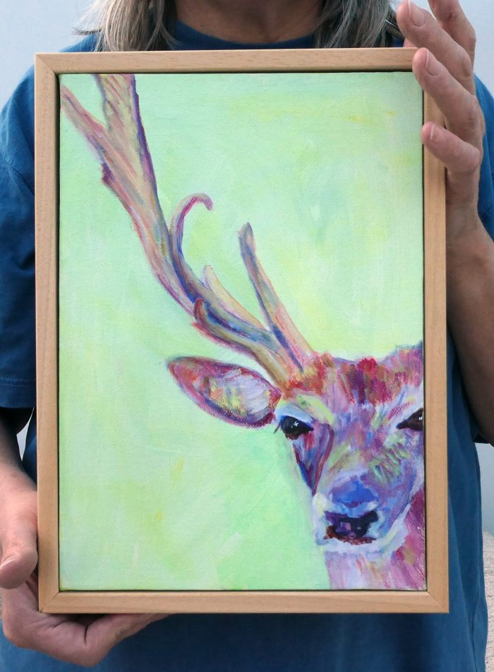 Framed stag painting held for scale