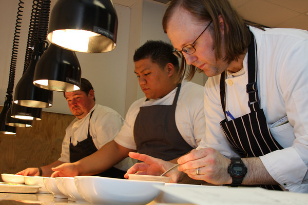 Image of three chefs working on a line with plates in front of them featuring celebrity chefs sean brock of husk restaurant and wylie dufresne and assistant