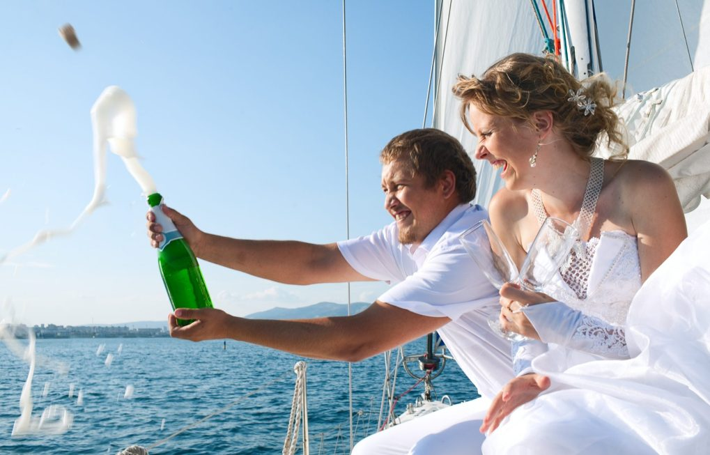 Bride and groom popping champagne cork on the deck of yacht