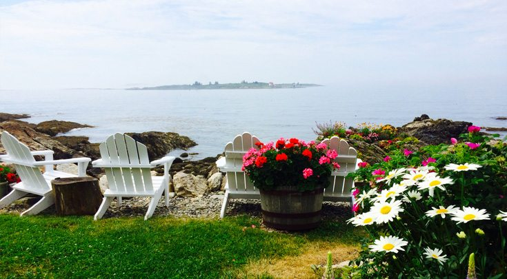 Four white adirondack chairs and flowers on viewpoint over an island off of Maine coast