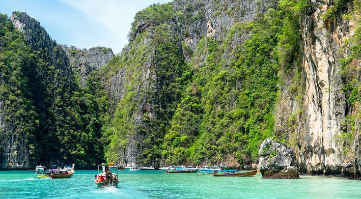 Thailand Asia boats paddling through water surrounded by cliffs
