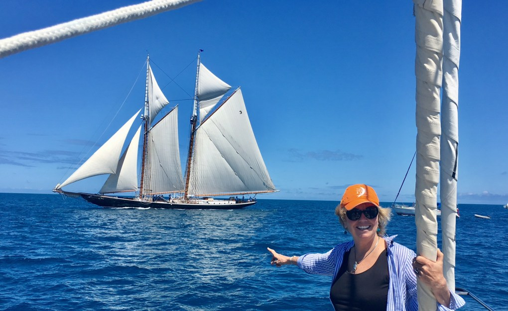 Carol Kent sailing on the S/Y EMILY MORGAN at the 2017 America's Cup in Bermuda pointing at the 141' S/Y COLUMBIA